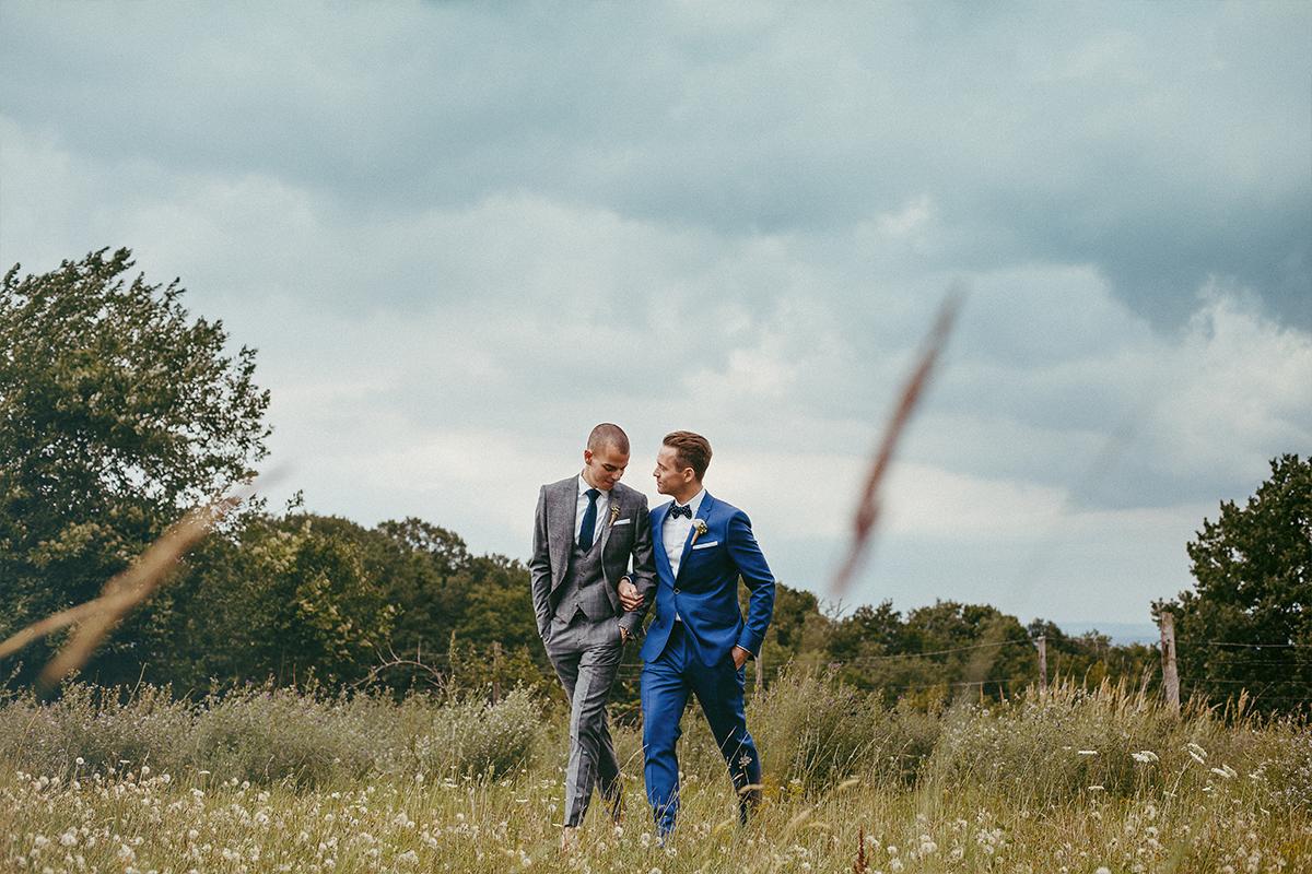 Hochzeitspaar mit zwei Bräutigamen geht über eine Wiese