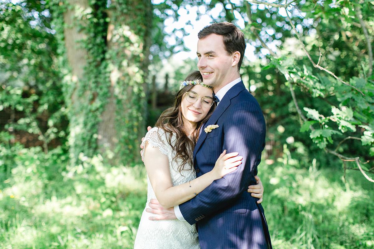Braut lehnt an Brust von Bräutigam im Wald