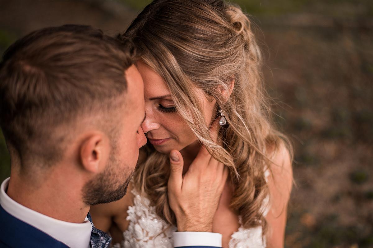 Ehepaar berührt sich mit der Stirn während Bräutigam die Braut am zärtlich am Hals berührt