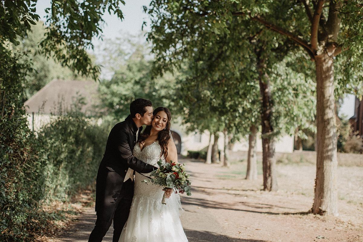 Bräutigam küsst lächelnde Braut auf die Wange im Wald