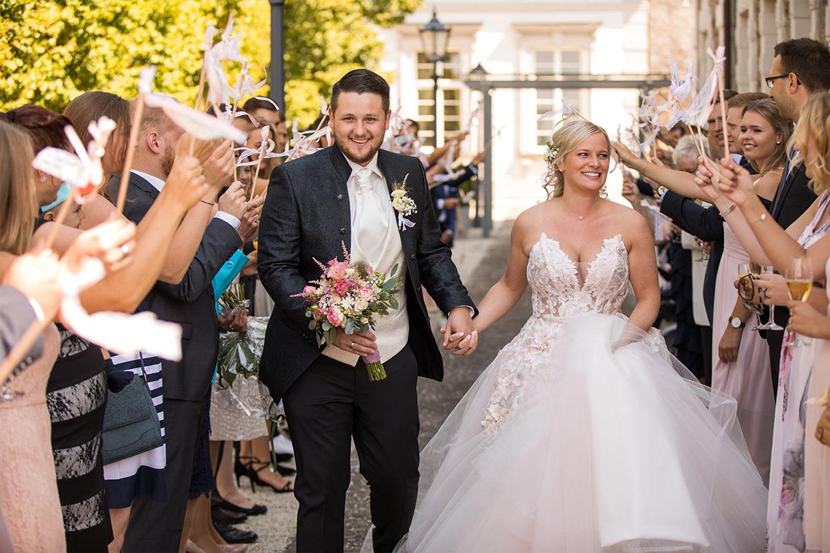 Lächelndes Hochzeitspaar geht durch Menschenmenge