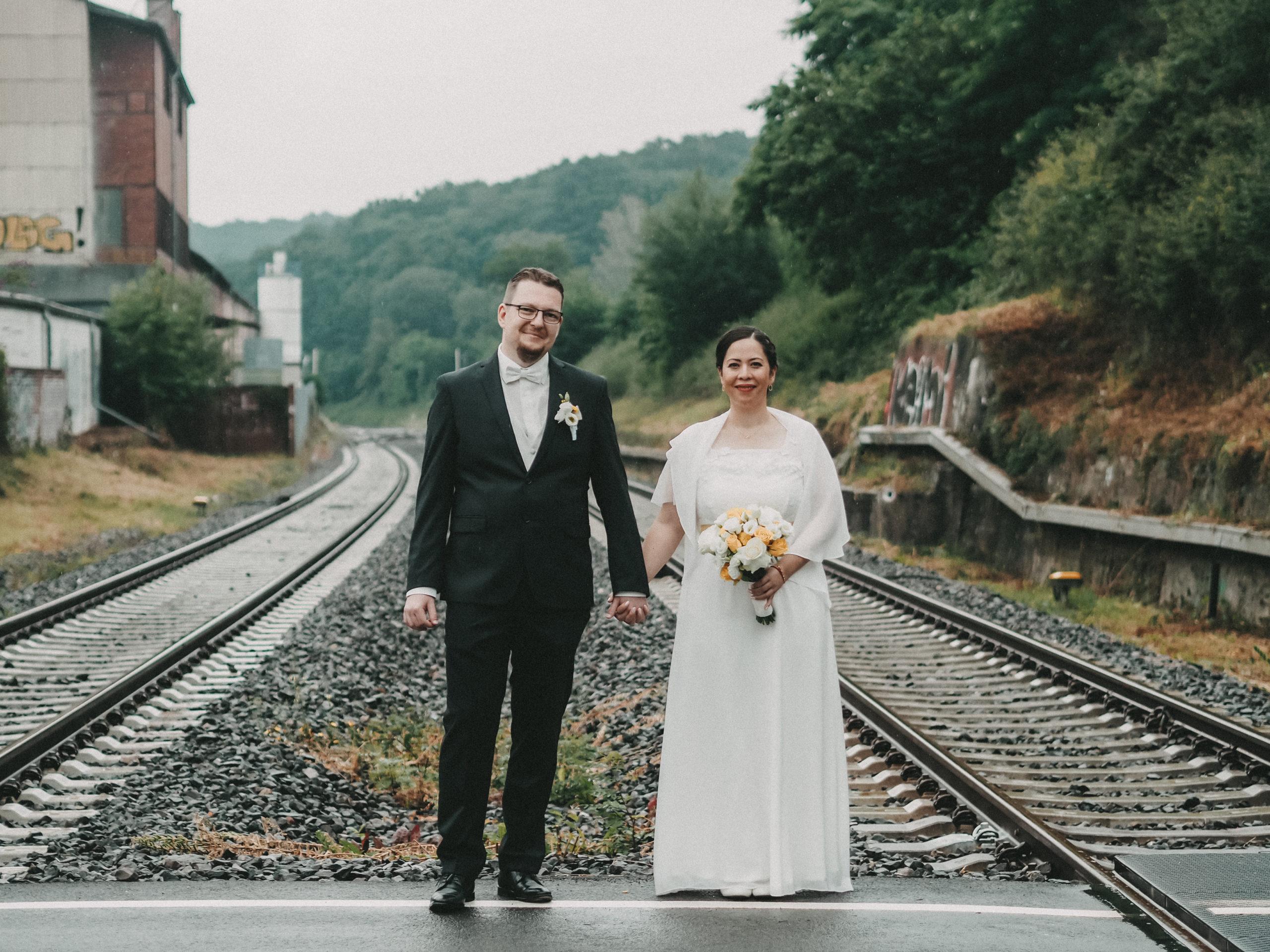 Hochzeitspaar zwischen Bahnschienen